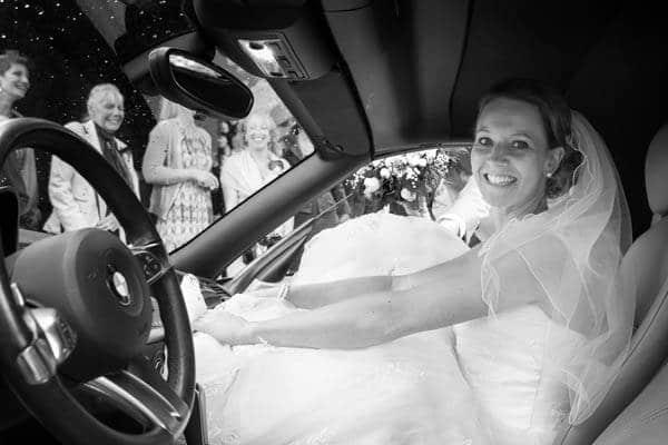 Een stralende bruid in de trouwauto