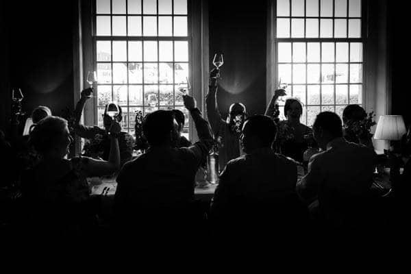 Een awardwinnende zwart/wit foto van een toost van een bruiloft