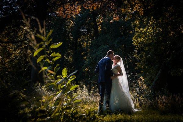 Een bruidspaar kussend tussen de bomen in tegenlicht