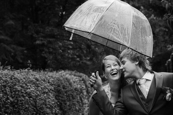 Bruidsfotograaf Putten. Een bruidpaar lachend onder een paraplu in de regen