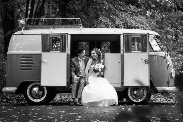 Een bruidspaar zittend in een volkswagen busje