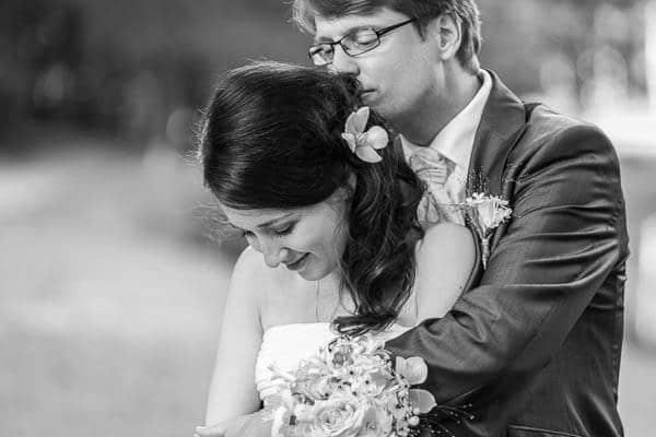 Een bruidegom kust de bruid op haar achterhoofd