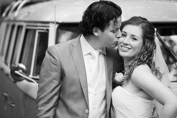 Een bruidegom kust de bruid op haar wang