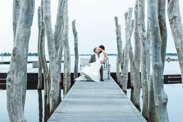 Een bruidspaar zittend op een steiger tijdens het blauwe uur