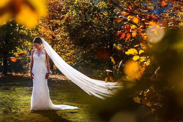 Trouwfotograaf Arnhem. Een bruid staand in de herfst tussen de bomen