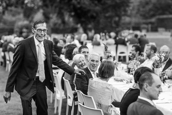 De vader van de bruidegom loopt langs lange tafels op een bruiloft buiten