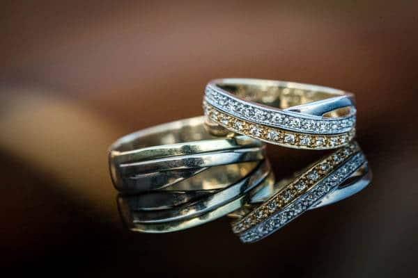 Close-up van trouwringen bezet met diamanten op spiegelende ondergrond