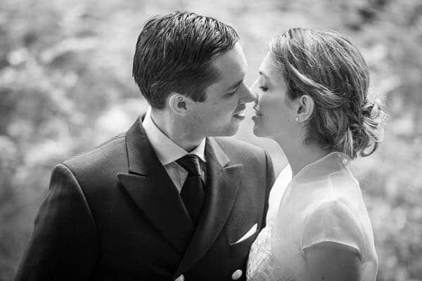 Een zwart / wit foto van een kussend bruidspaar