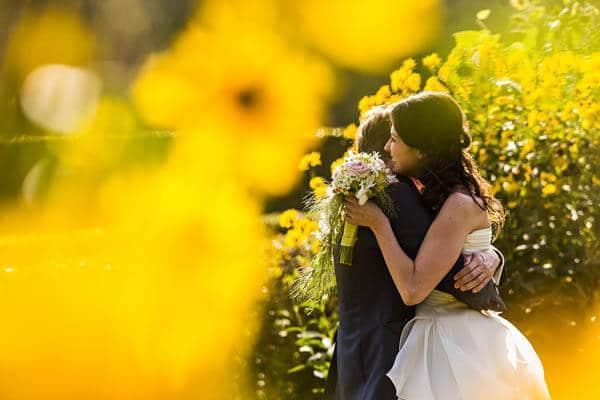 Trouwfotograaf Nijkerk. Een bruidspaar in omhelsing tussen de gele bloemen