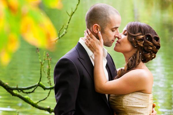 Fotograaf Bruiloft Staverden. Een kussend bruidspaar geposeerd voor groen water