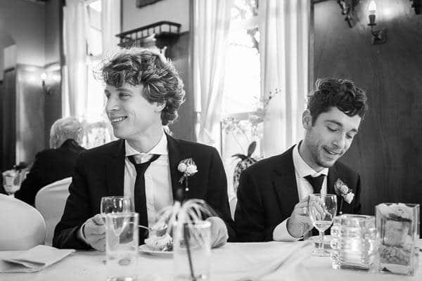 Fotograaf Bruiloft Zwolle. Twee mannen zitten aan een tafel te eten tijdens een diner op een bruiloft