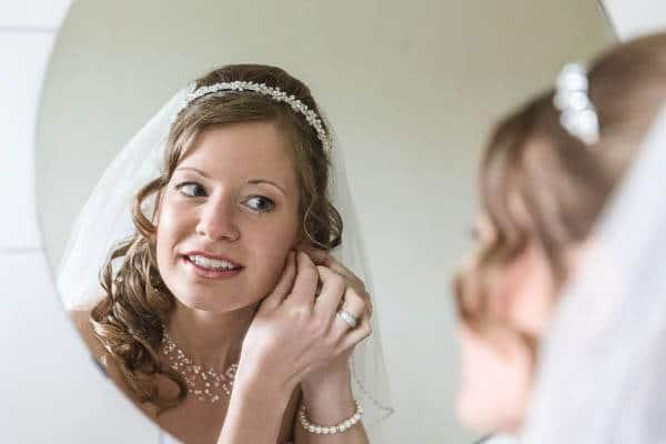 Een bruid doet haar oorbellen in voor de spiegel