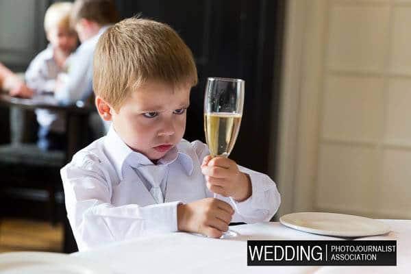 Een jongetje kijkt naar een glas drinken op een bruiloft