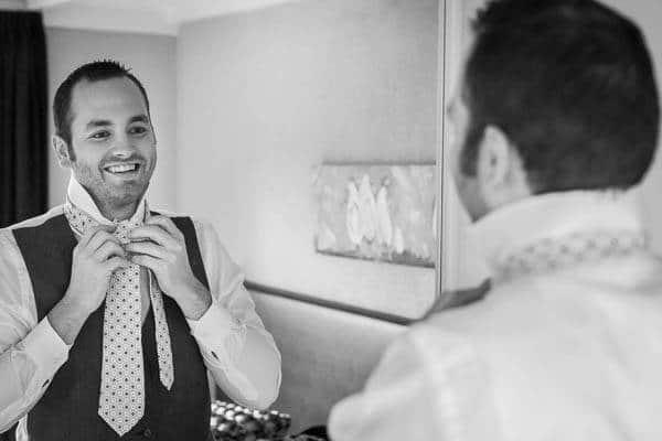 Een bruidegom doet zijn stropdas om