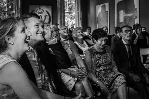 Een lachend bruidspaar tijdens de ceremonie