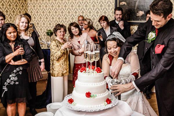 Bruidsfotograaf Barneveld. Een bruidspaar snijdt de bruidstaart aan.