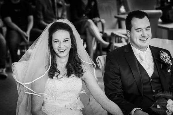 Een vrolijk bruidspaar tijdens de huwelijksvoltrekking
