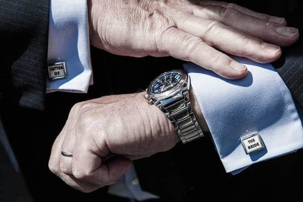 De vader van de bruid met manchetknopen kijkt op zijn horloge