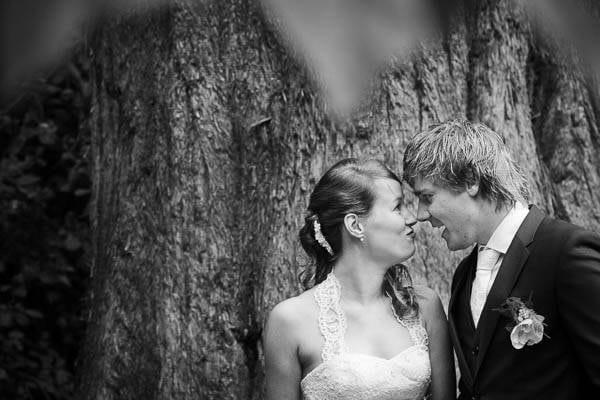 Een bruidspaar bij een boom in een park