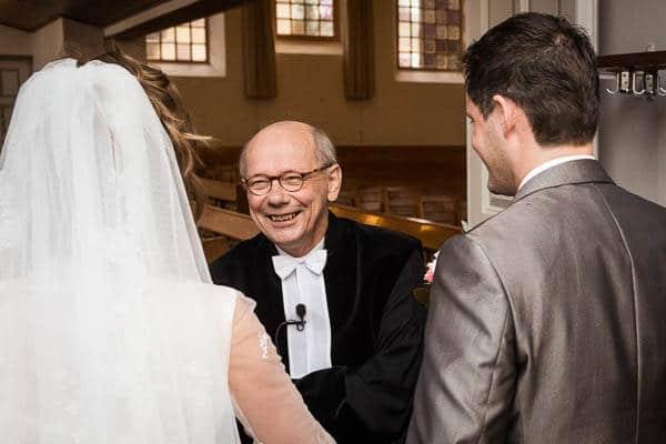 De dominee ontvangt een bruidspaar voor een bruiloft in de kerk