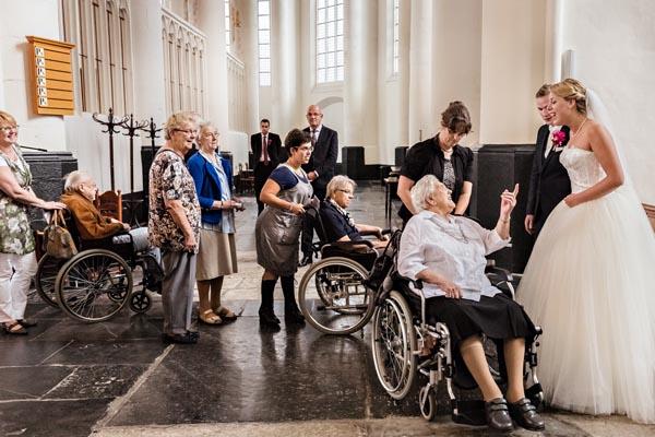 Bruidsfotograaf Utrecht. Gasten in een kerk tijdens een bruiloft feliciteren het bruidspaar