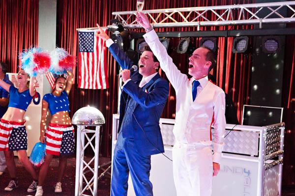 Een homoseksueel bruidspaar proost met de gasten tijdens een feest. LGHBT