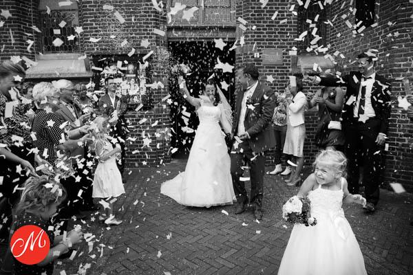 Bruidsfotograaf Harderwijk. Een bruidsmeisje schrikt van de confetti in Harderwijk