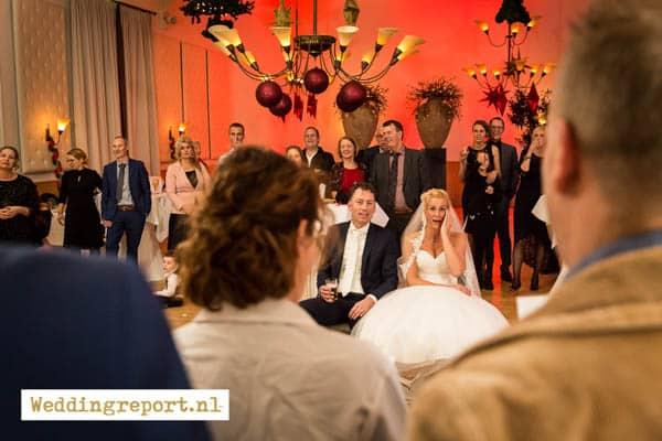 Het bruidspaar geniet van een stukje opgevoerd door de gasten in de trouwzaal van Groot Warnsborn Arnhem