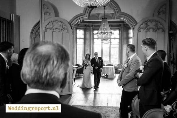 Bruid komt trouwzaal binnen met stiefvader in Kasteel de Schaffelaar in Barneveld